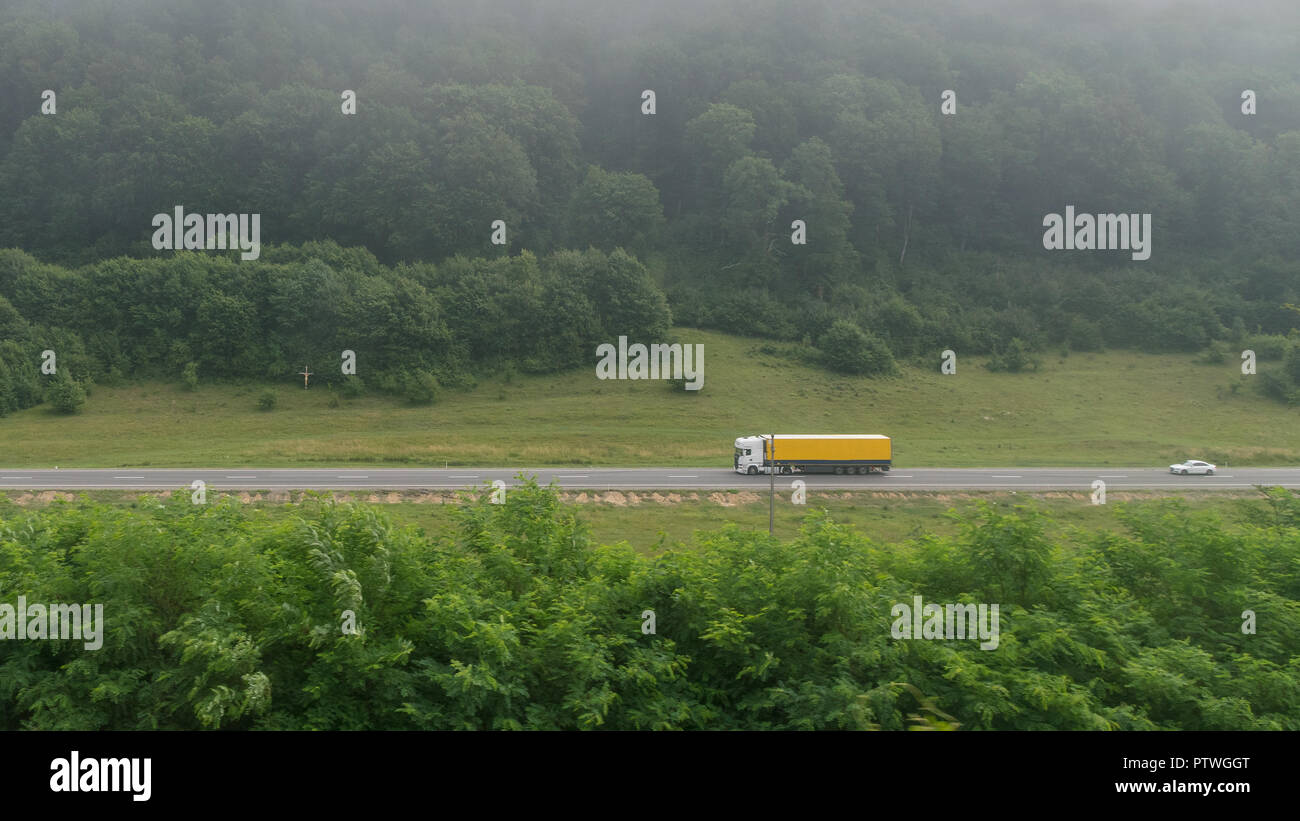 A truck on a road near a forest mountain in fog. - Stock Image