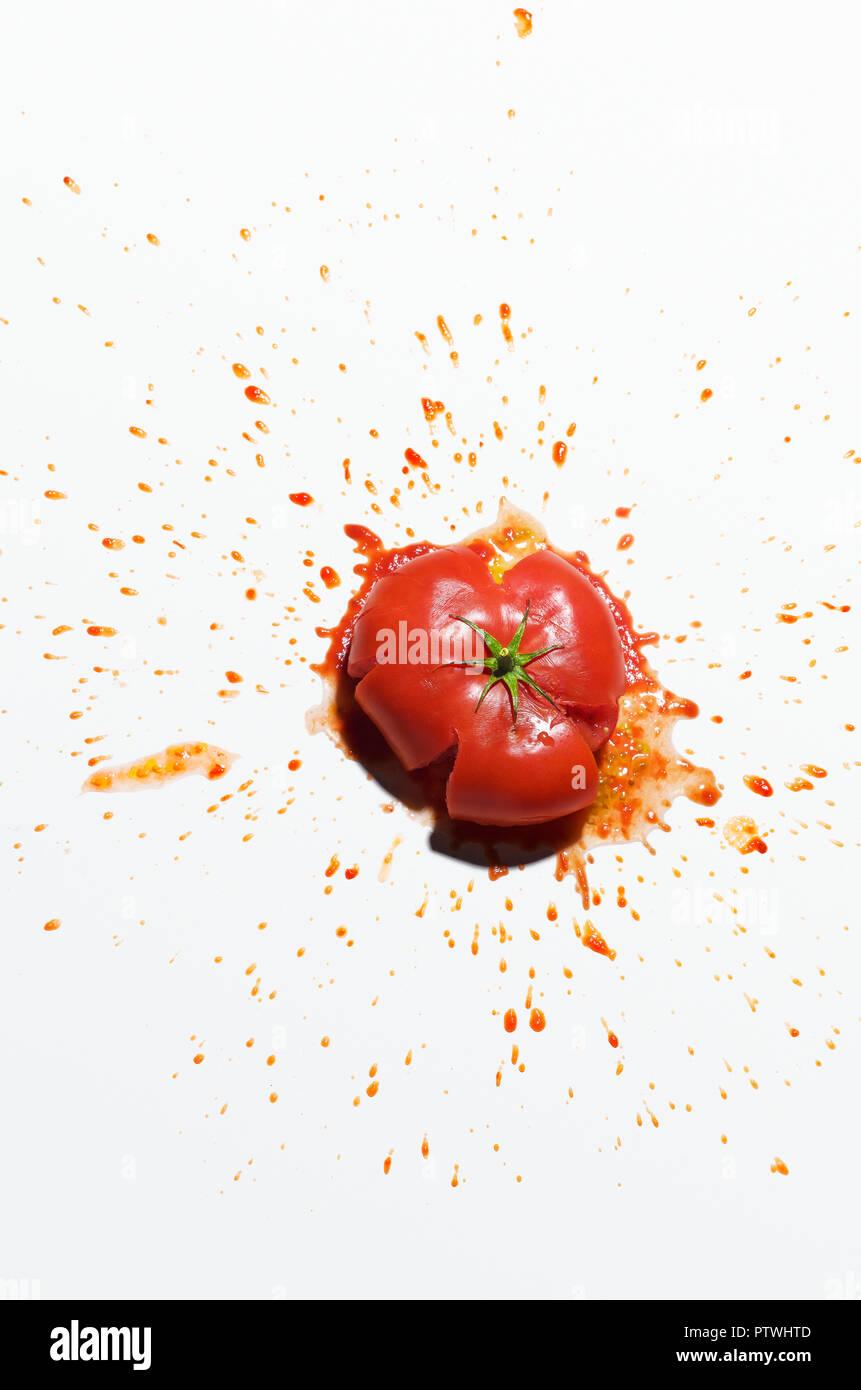 Fresh red tomato splattering juice against white background - Stock Image