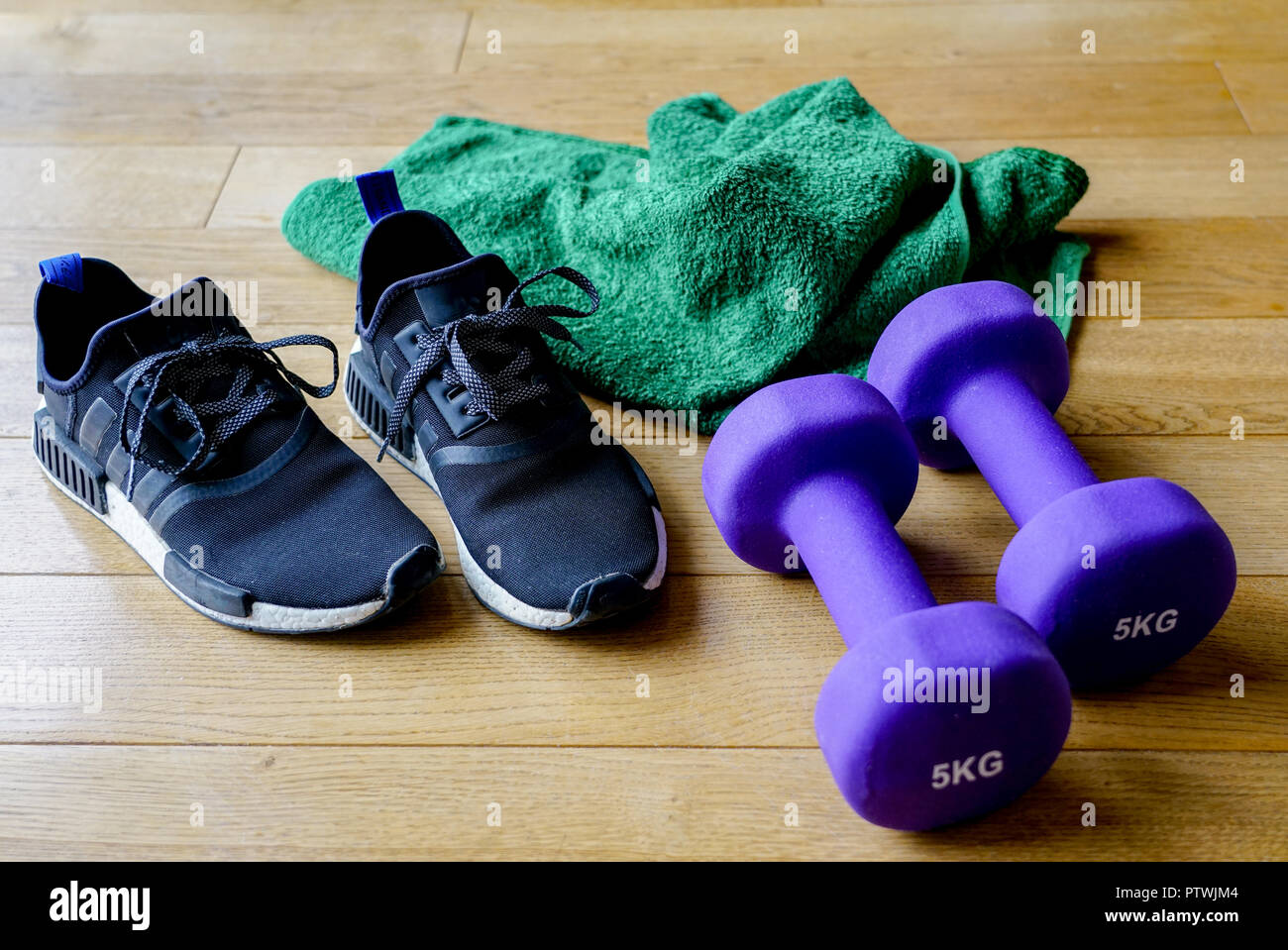 purple dumbbells, green towel and black sports shoes Stock Photo