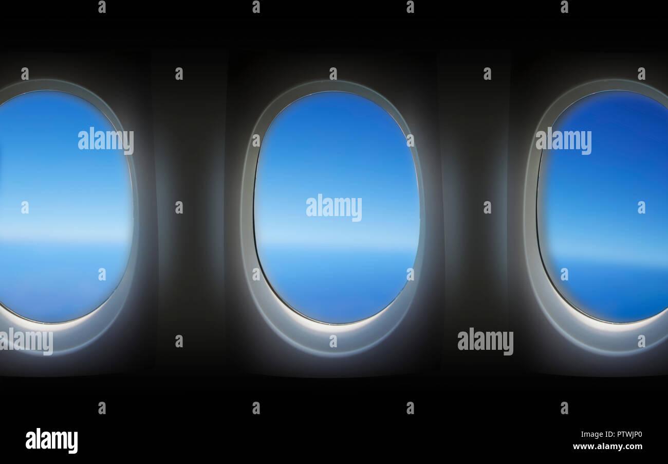 View through aeroplane window towards clear blue sky - Stock Image