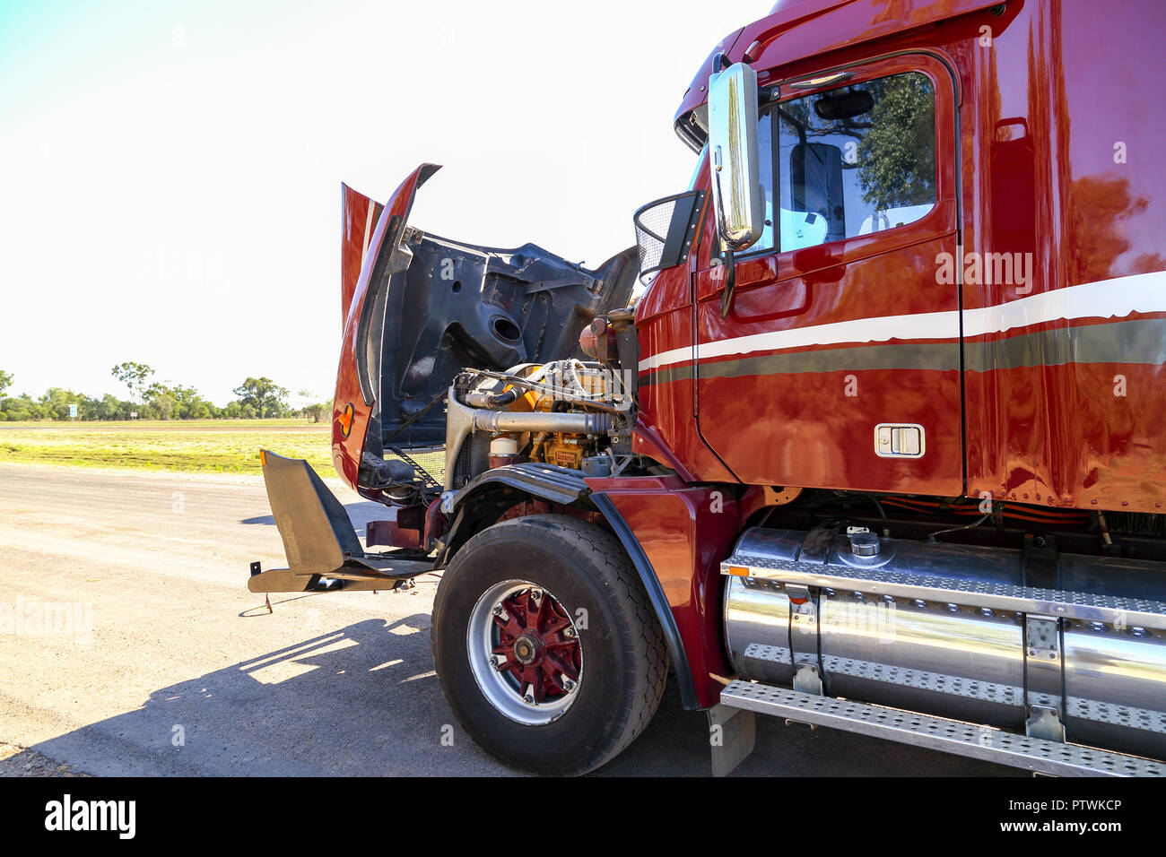 A red or maroon semi-trailer broken down with bonnet up. - Stock Image