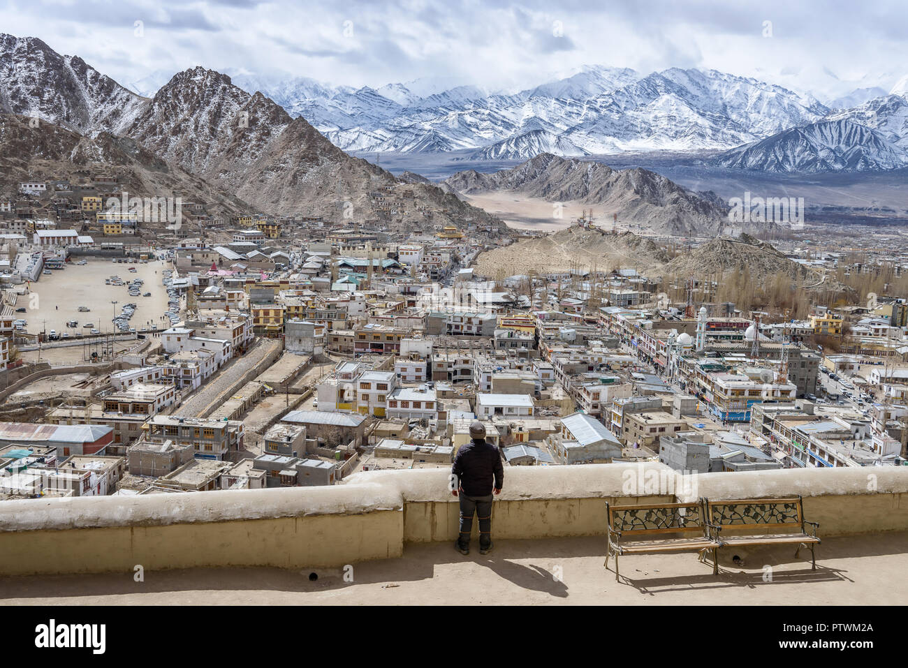 Man enjoying the views of Leh Ladakh in India, cityscape of the city Leh in Jammu and Kashmir, beautiful snow-capped mountains in Himalaya. High altit - Stock Image