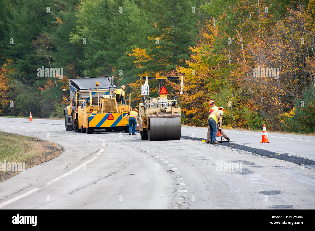 A road maintenance project in the Adirondack Mountains, NY USA with a dump truck, a paving machine, a roller and a construction crew. - Stock Image