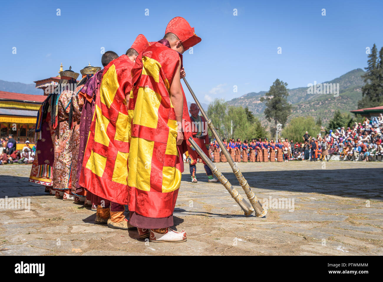Monks making music with trumpets for colorful mask dance at yearly Paro Tsechu festival in Bhutan - Stock Image
