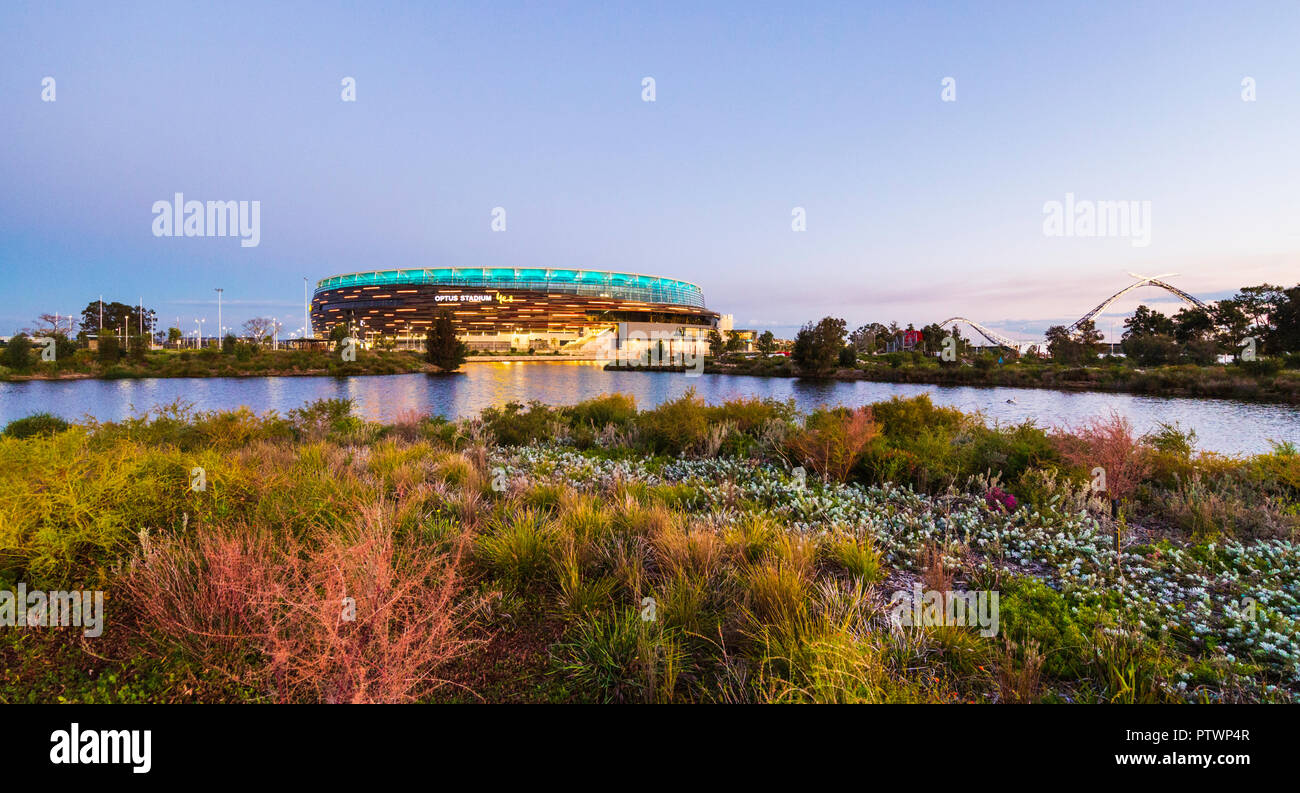 Optus Stadium surrounded by a lake and parkland. - Stock Image