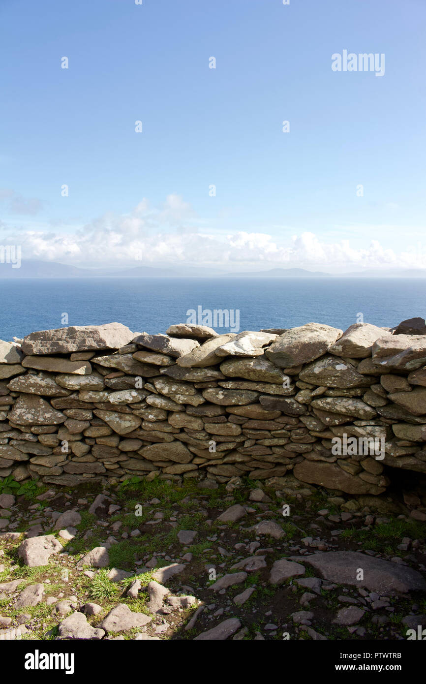 Stone wall of a primitive clochán (beehive hut) dwelling on the Dingle Peninsula in County Kerry, Ireland overlooking the Atlantic Ocean - Stock Image