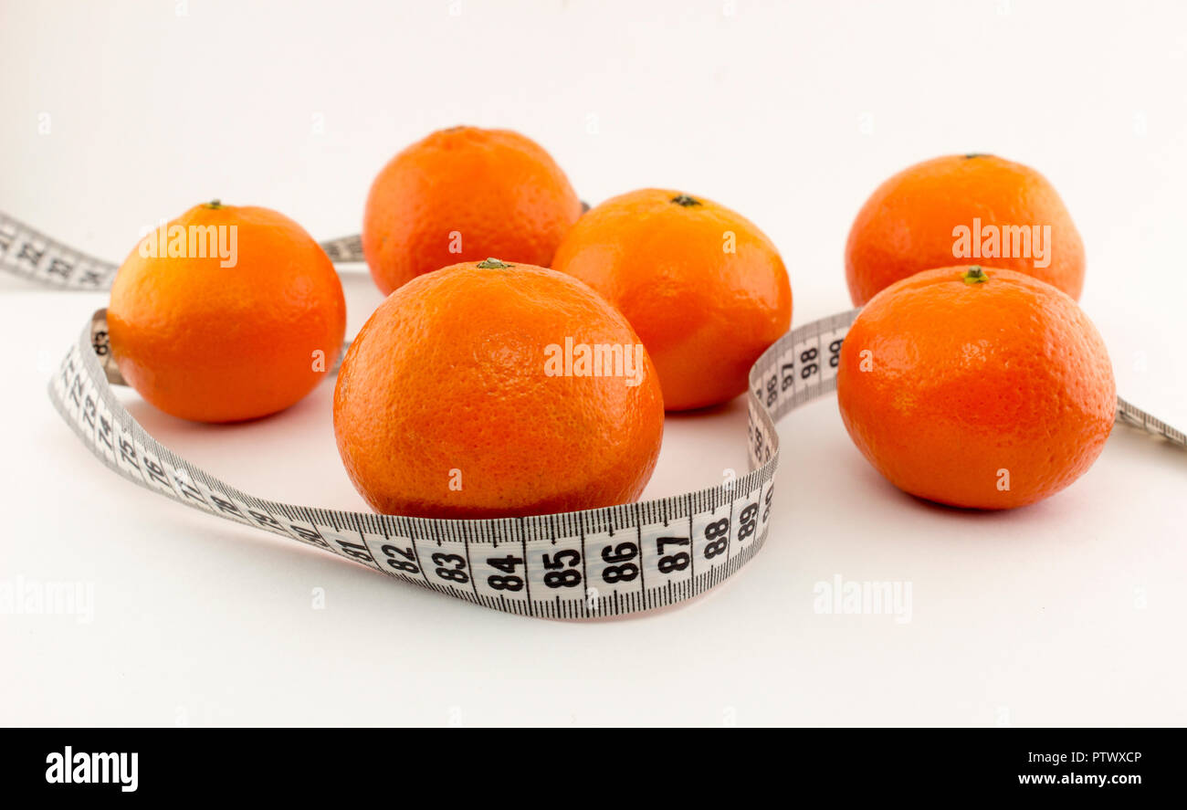 Mandarins and centimeter tape on a white background - Stock Image
