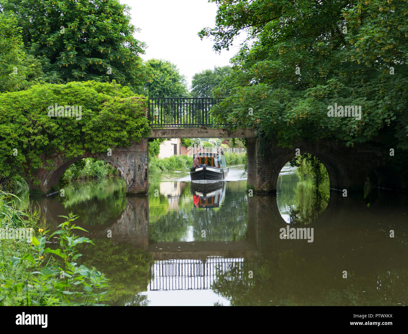 A narrow boat approaches a picturesque bridge on the River Way near Godalming in Surrey, England. - Stock Image