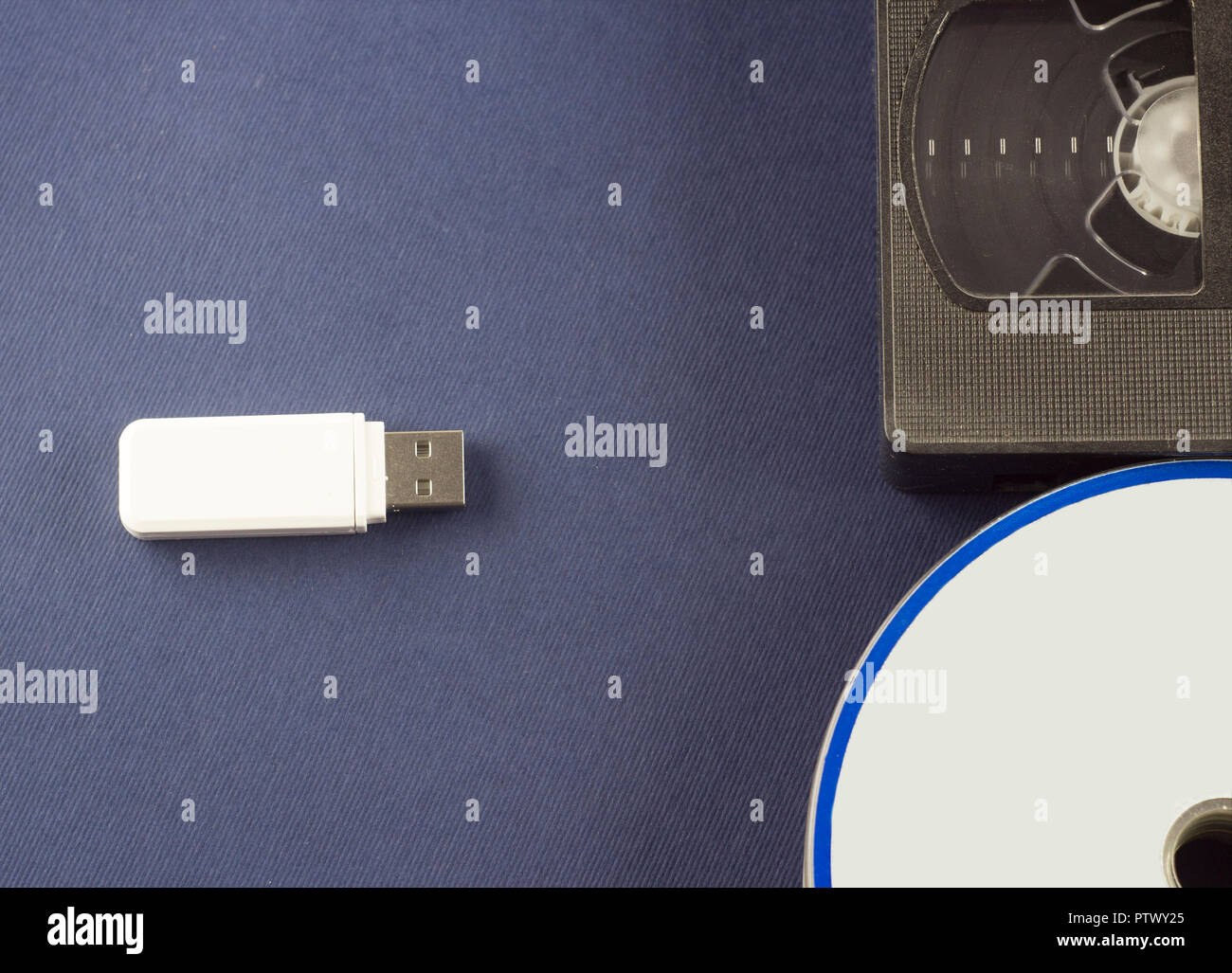 Flash drive on a blue background discs and video cassette - Stock Image