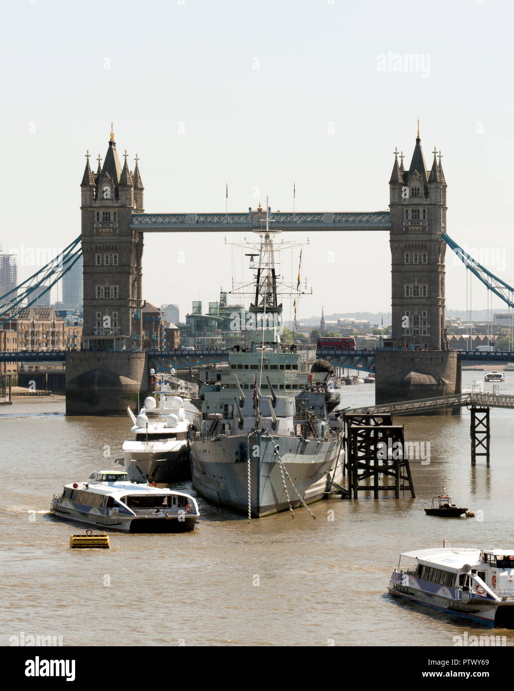 Royal Navy warship HMS Belfast moored on the River Thames in front of Tower Bridge, London, England. - Stock Image