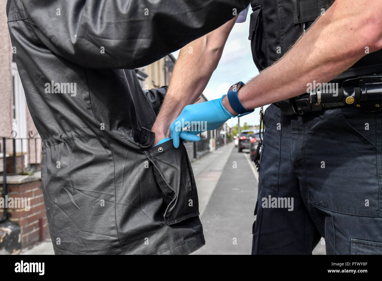 A Merseyside Police officer searches a man's pockets as he conducts a Stop and Search in the Bootle area of Liverpool - Stock Image