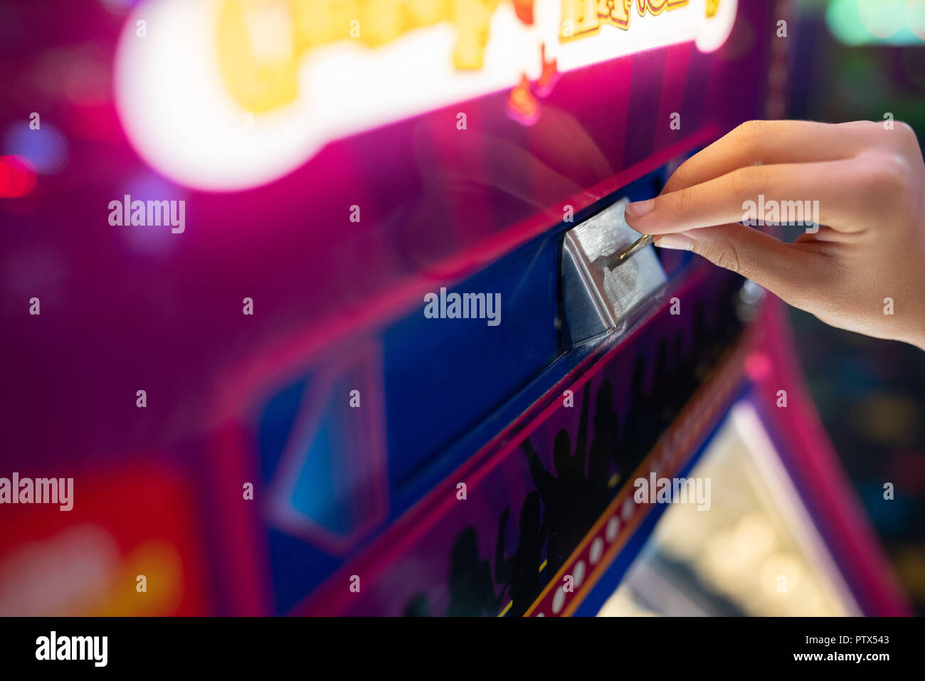 Child hand inserting a coin into the amusement park arcade machine. - Stock Image