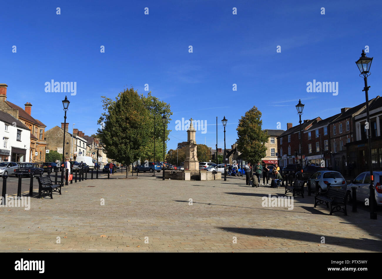 On a beautiful autumn morning the sun shines down on the Market Street in Brackley in Northamptonshire, as people are out and about. Stock Photo