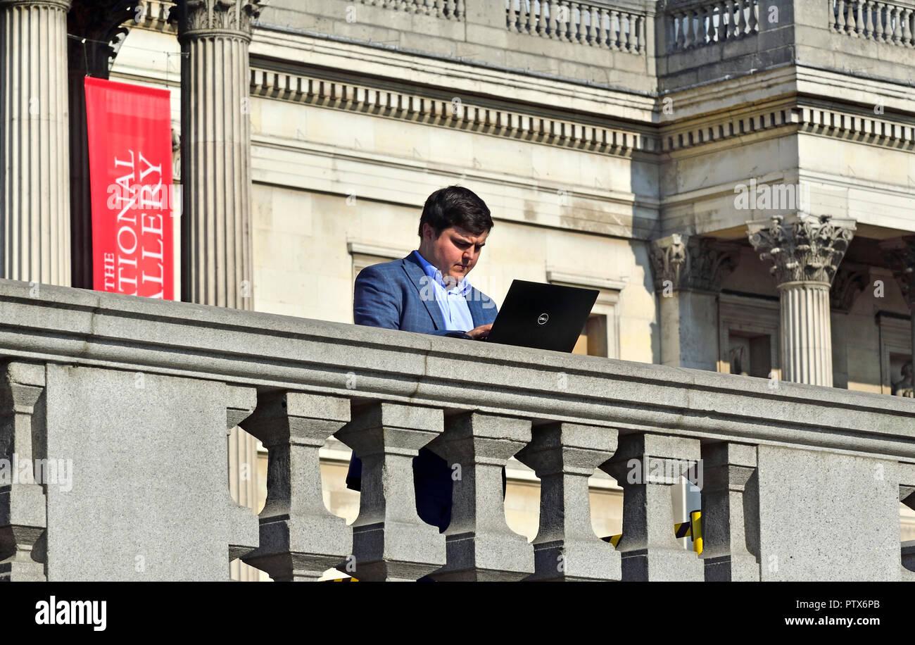 Businessman using his laptop computer in Trafalgar Square, London, England, UK. - Stock Image