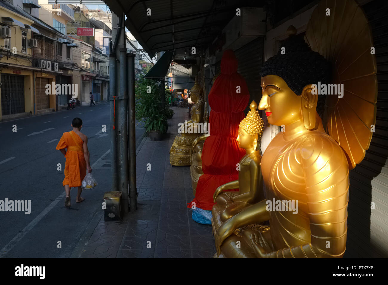A Thai Buddhist monk passing Buddha statues outside a shop for religious objects in Bamrung Muang Rd., Bangkok, just after sunrise - Stock Image