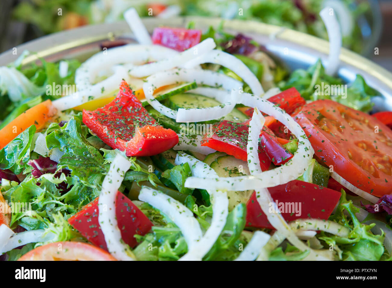Fresh and healthy mixed salad with lettuce, red peppers, tomatoes and onions, as a starter, side dish or first course for a vegetarian or vegan diet Stock Photo