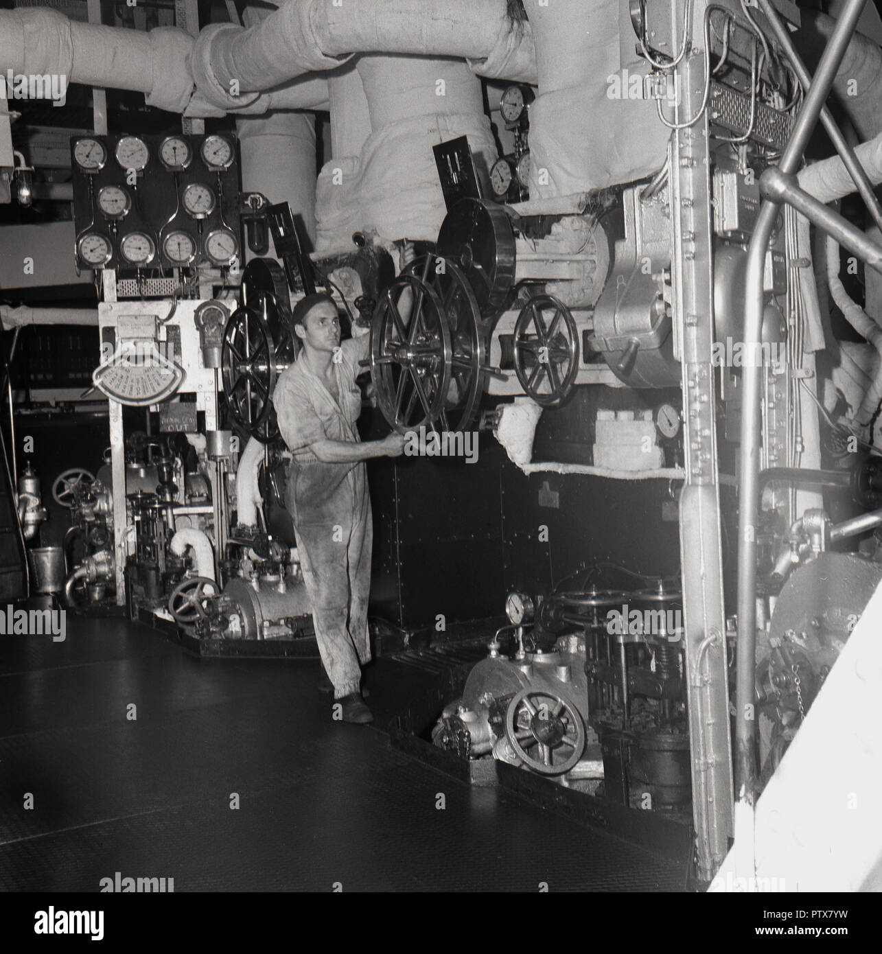 1950s, historical, seaman or oiler turning a wheel while working below deck in the engine room of a steamship. An area of complicated machinery and pressure systems wokring together to move the ship, the technician is a vital member of the ships' crew. - Stock Image