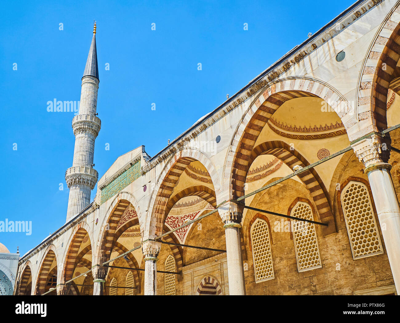 Arcaded courtyard of The Sultan Ahmet Camii Mosque, also known as The Blue Mosque, with a minaret in the background. Istanbul, Turkey. - Stock Image