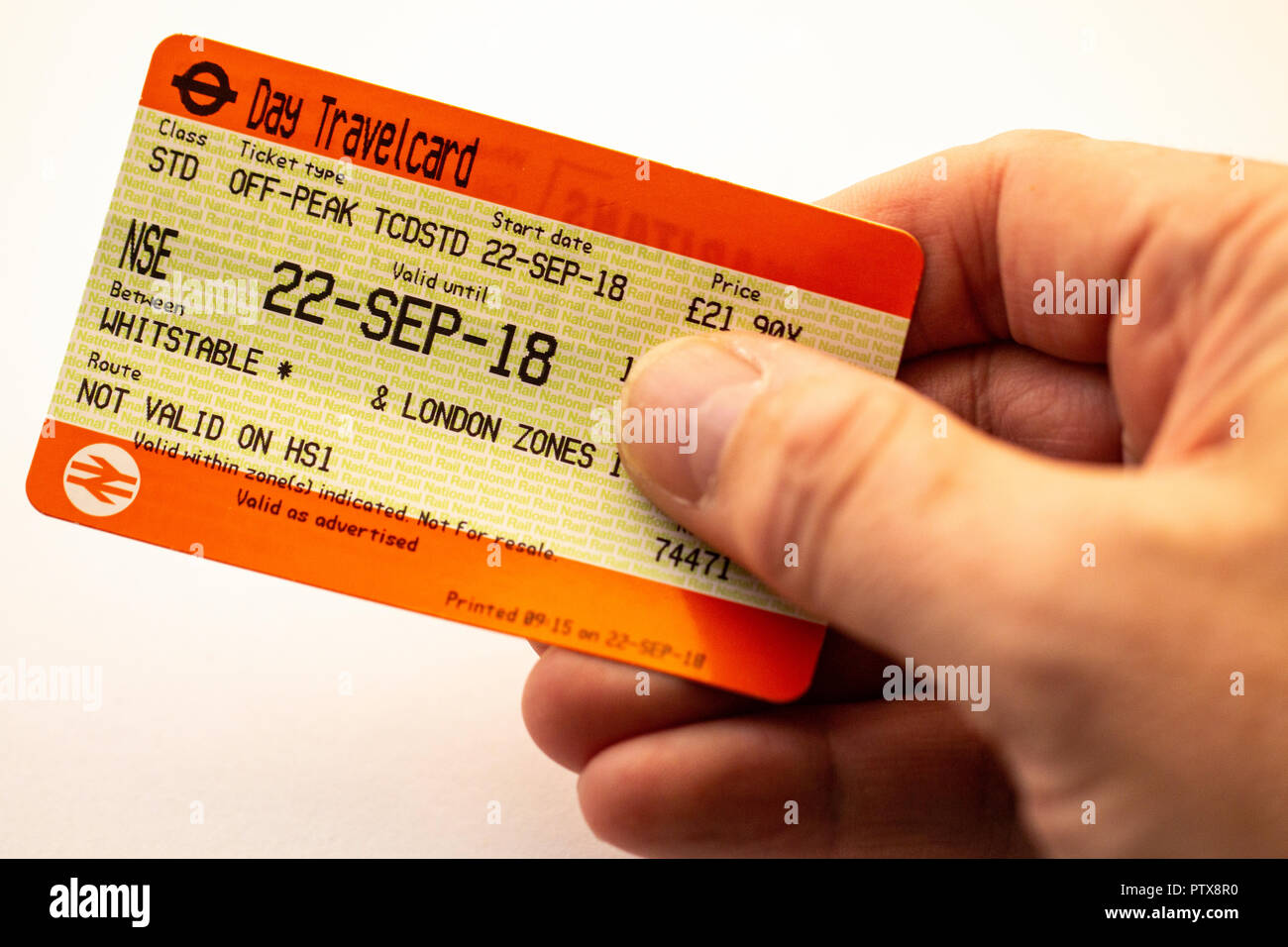 Hand holding British railway ticket, standard off peak one day