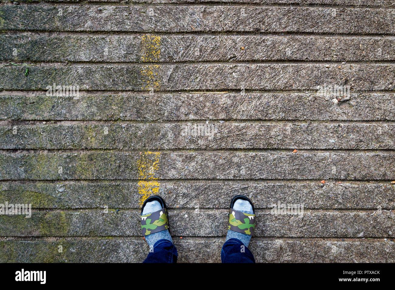 Socked Slippered Feet On Stone Pavement - Stock Image