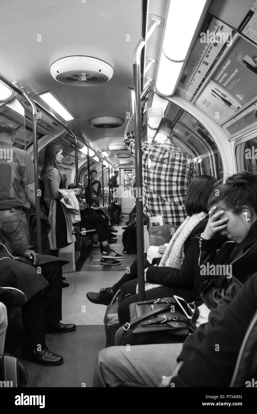 Black & white, portrait shot: passengers inside tube train; commuters standing & seated. Anxious young lady with earphones has face palming gesture. - Stock Image