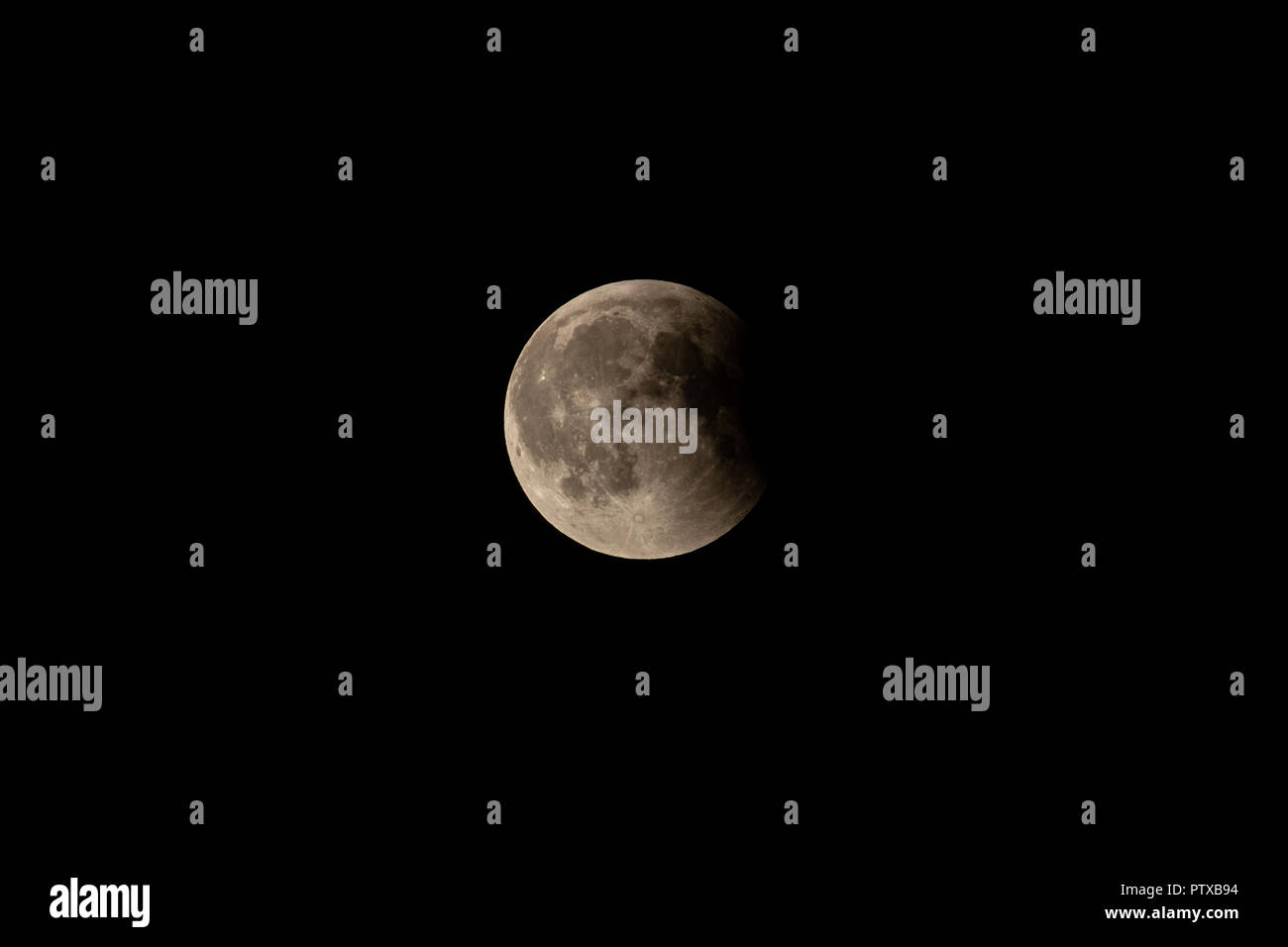 Partially eclipsed full moon, long shot, black sky - Stock Image