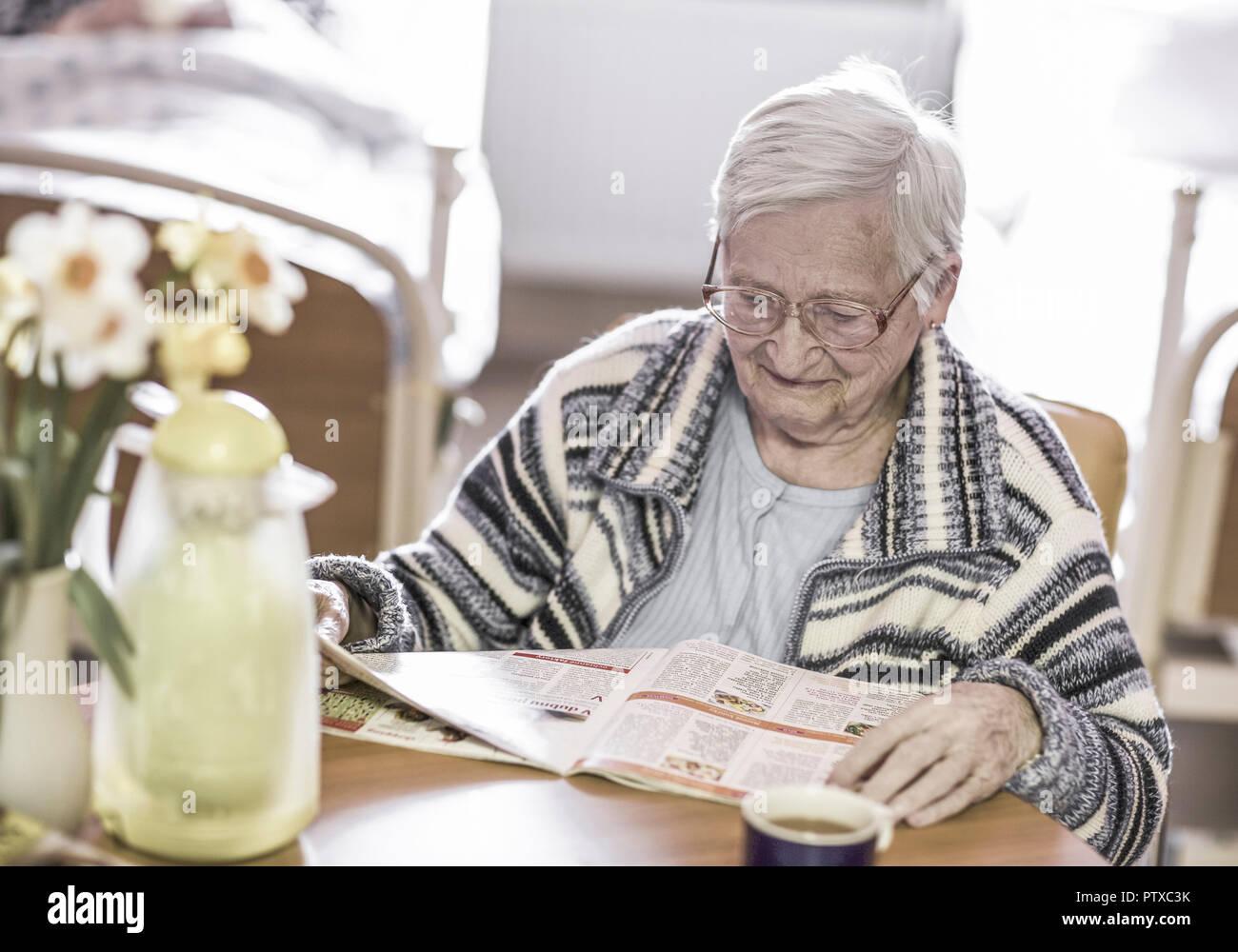 Altenheim, Seniorin liest Zeitung (model-released) Stock Photo