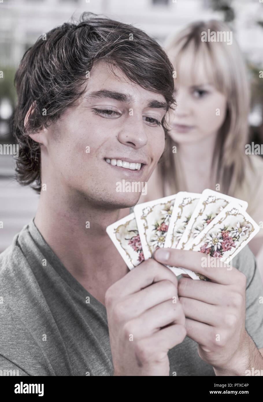 Junges Paar beim Kartenspielen, sie schaut in seine Karten (model-released) - Stock Image