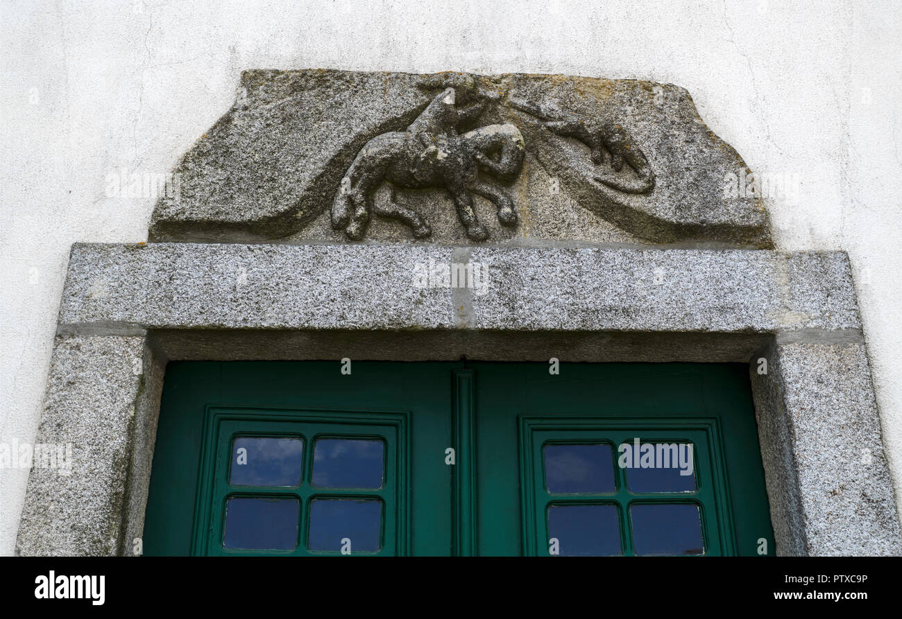 Granite stone with a bas-relief sculpture of St George Killing the Dragon on top of a door in the historic centre of Trancoso, Portugal Stock Photo