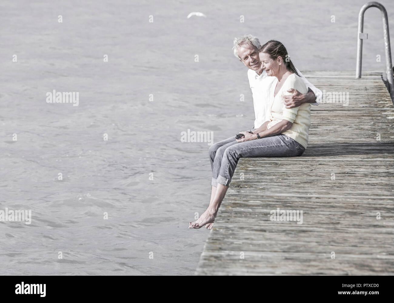 Seniorenpaar, sitzen auf Steg an See (model-released) - Stock Image