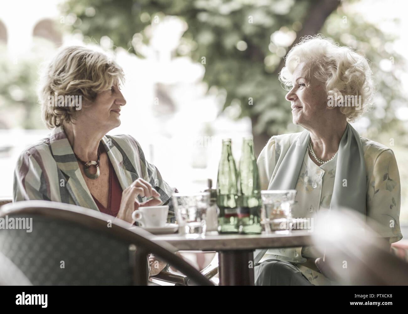 Zwei Seniorinnen sitzen in Strassencafe (model-released) - Stock Image