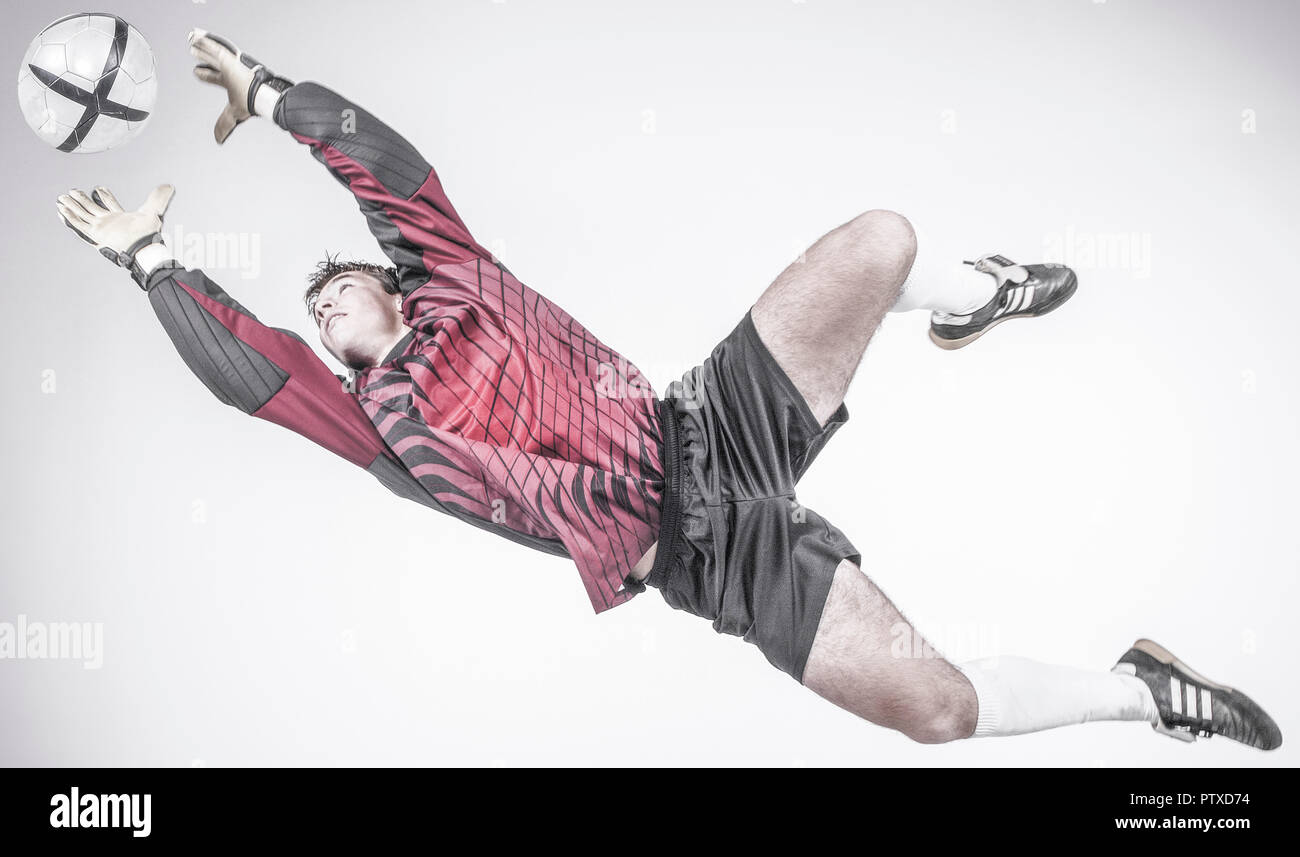 Fussball-Torwart, im Sprung nach dem Ball (model-released) - Stock Image