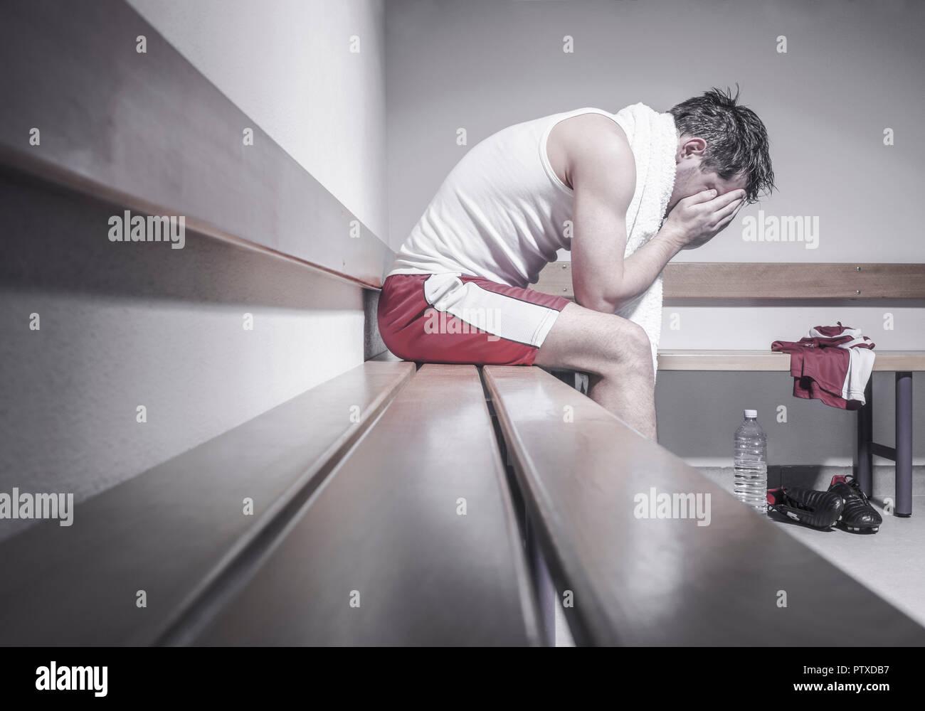 Fussballspieler in Umkleidekabine, niedergeschlagen (model-released) - Stock Image