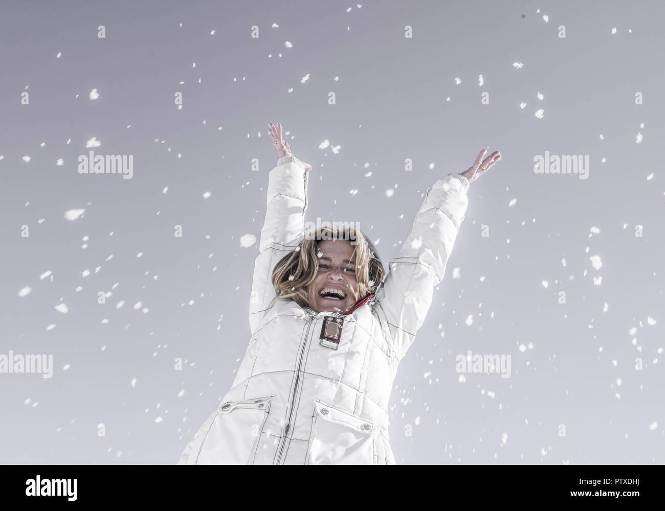 Seniorin wirft lachend Schnee in die Luft (model-released) Stock Photo