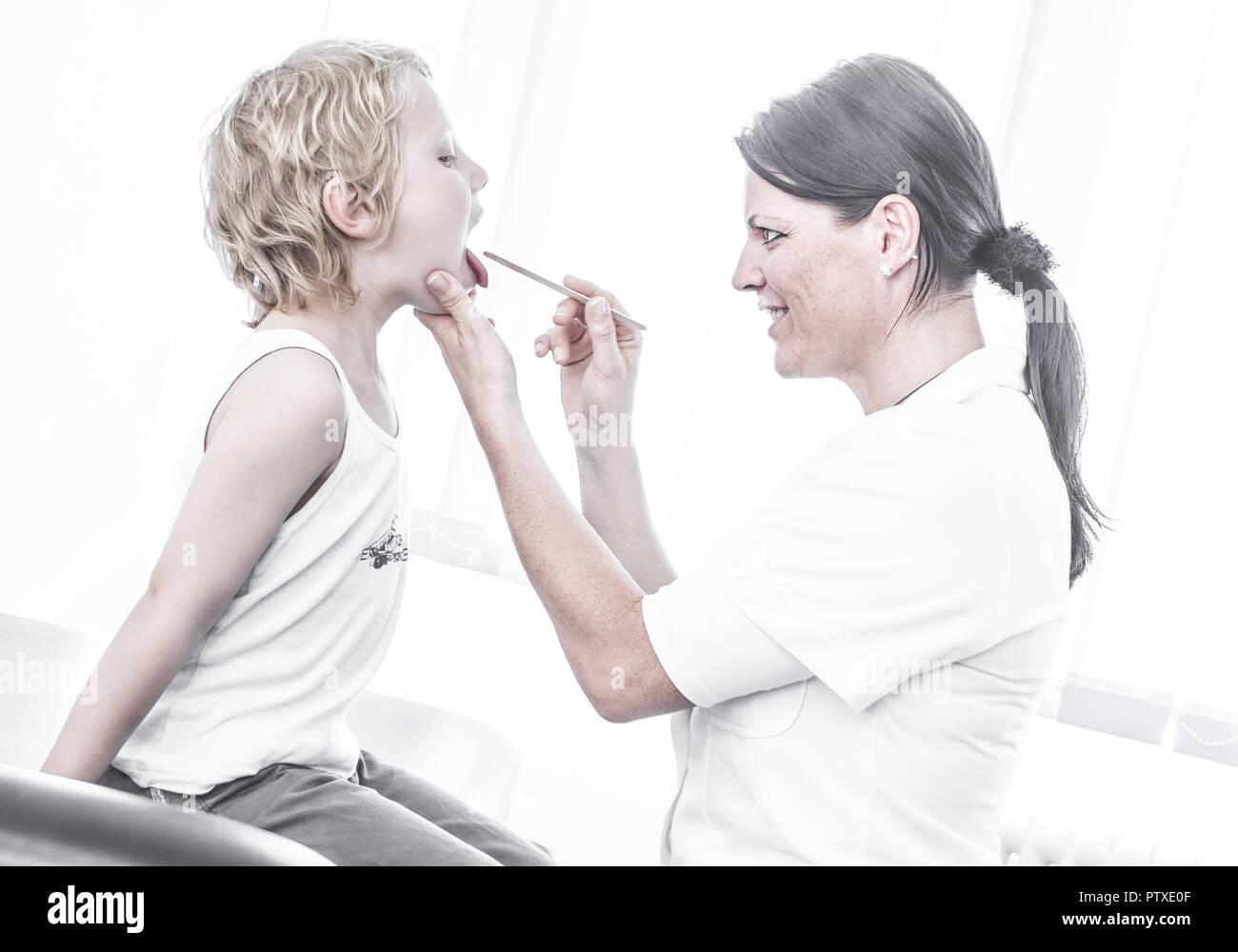 Aerztin sieht kleinem Jungen in den Hals (model-released) - Stock Image