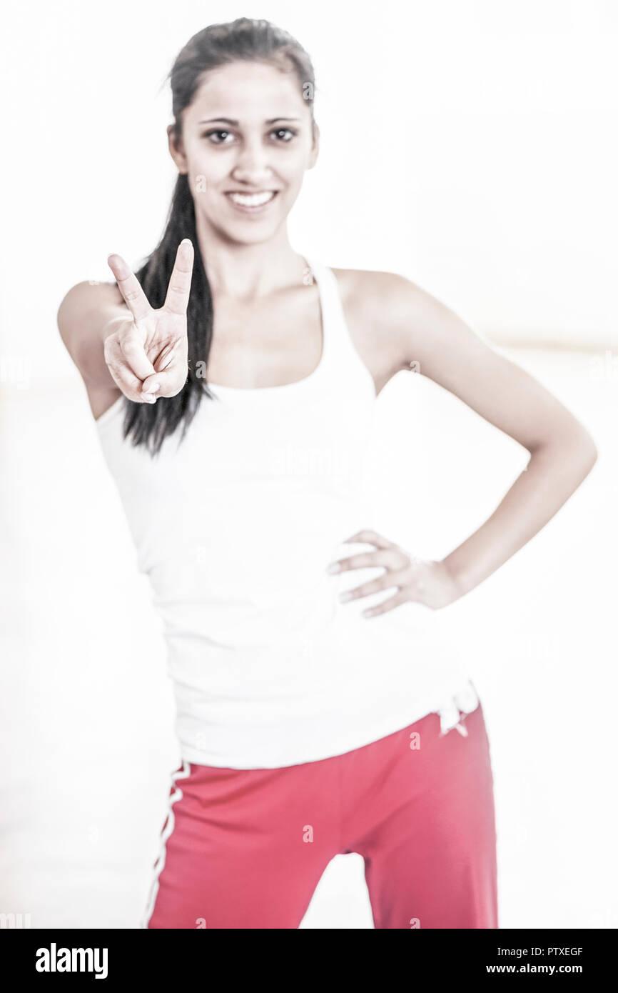 Junge Sportlerin macht Victory-Zeichen (model-released) - Stock Image