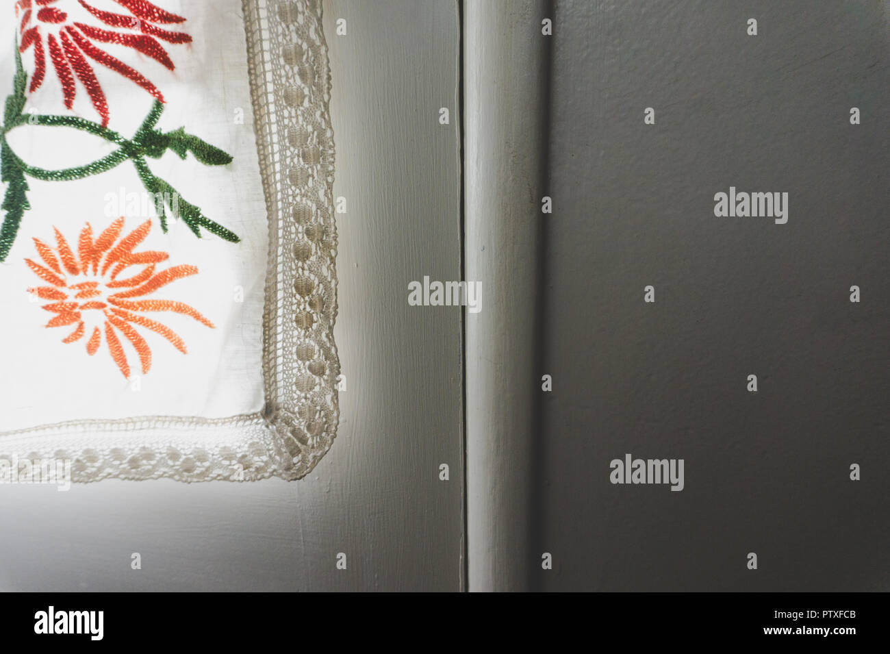 Close-up of Shabby Chic lacey flowery curtain illuminated by sunlight against a white wall with room for copy - Stock Image
