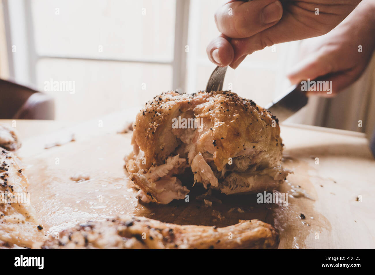 Close-up of perfectly roasted chicken being carved in gourmet kitchen natural light. Will make you hungry! - Stock Image