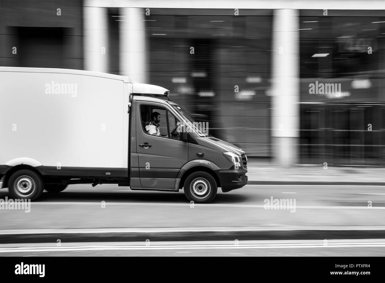 Van speeding in central London in blurred motion. Deliberately blurred to convey speed. - Stock Image