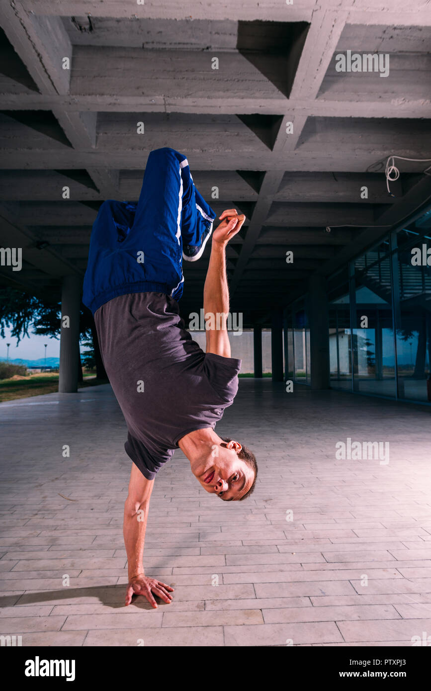 Sportive man training parkour handstand outdoor - Stock Image