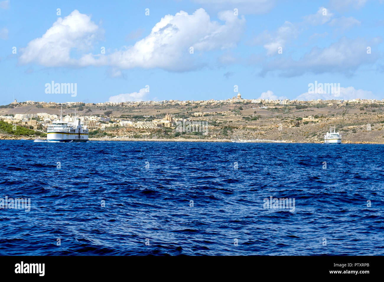 Two Gozo inter-island ferries on passage between Malta and Gozo. Gozo and MGarr ferry port on horizon - Stock Image