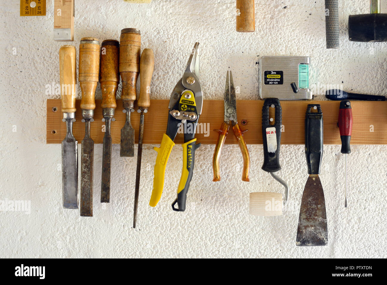 Woodworking Tools & Hand Tools including Chisels and Pliers Hanging in Workshop or Garage Wall-Mounted Tool Rack - Stock Image
