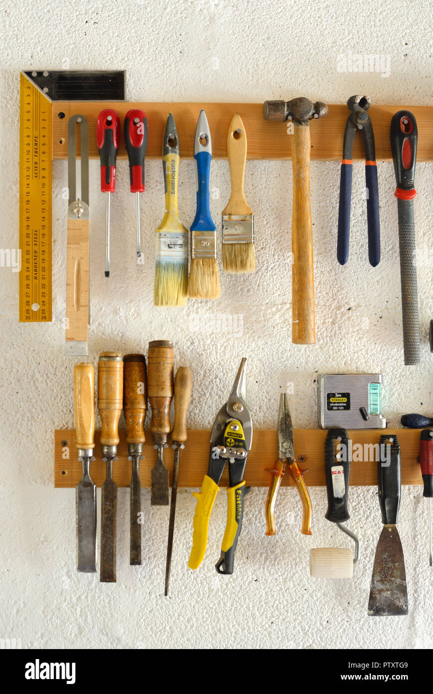 Woodworking Tools & Hand Tools including Paint Brushes, Chisels, Pliers and Hammers Hanging in Workshop or Garage Wall-Mounted Tool Rack - Stock Image