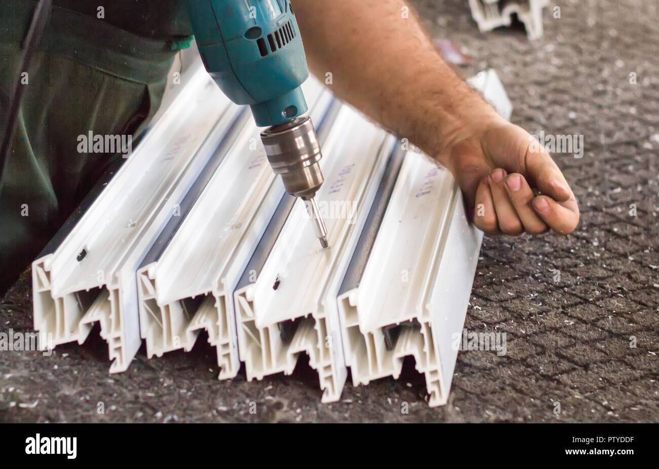Production of pvc windows, man fastens metal profile to plastic, close-up, to screw a screwdriver, plastic - Stock Image