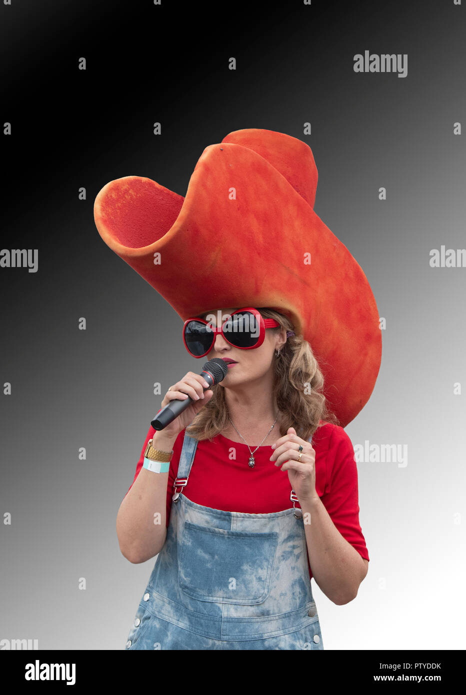 Portrait of a pretty female singer holding a microphone and wearing a giant red hat and huge red sunglasses - Stock Image