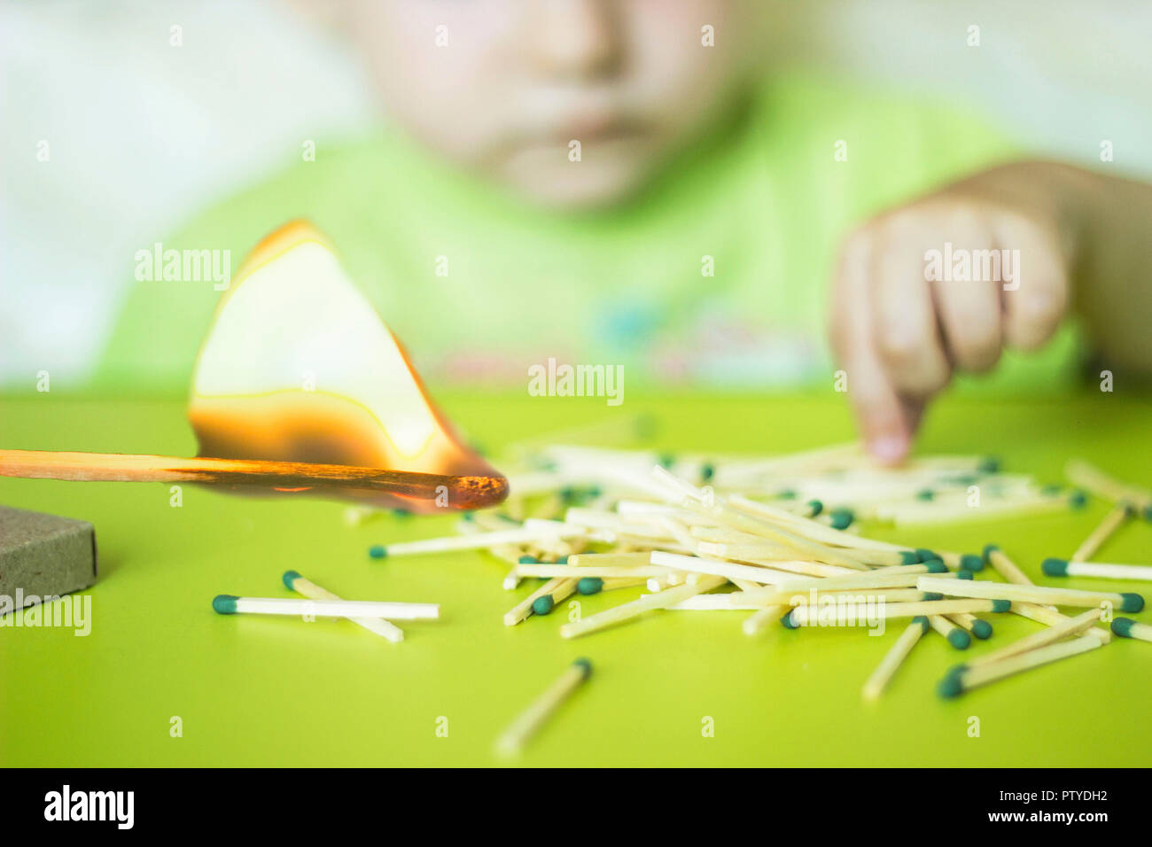 A child plays with matches in the foreground a burning match, a child and matches, a fire, dangerous - Stock Image