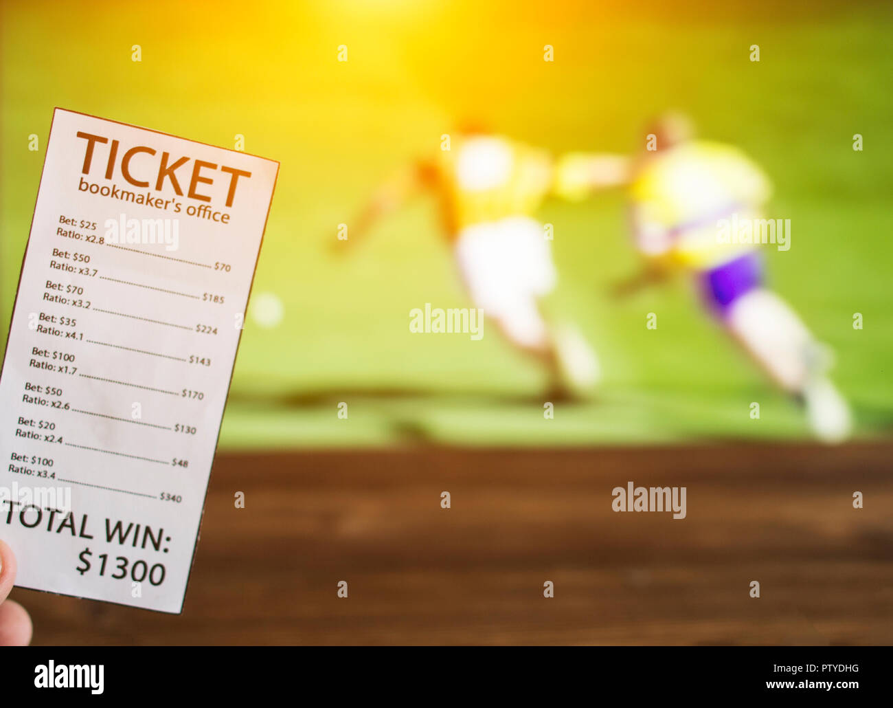 Bookmaker ticket on the background of the TV on which the sport is shown in the game of hurling, sports betting, bookmaker - Stock Image