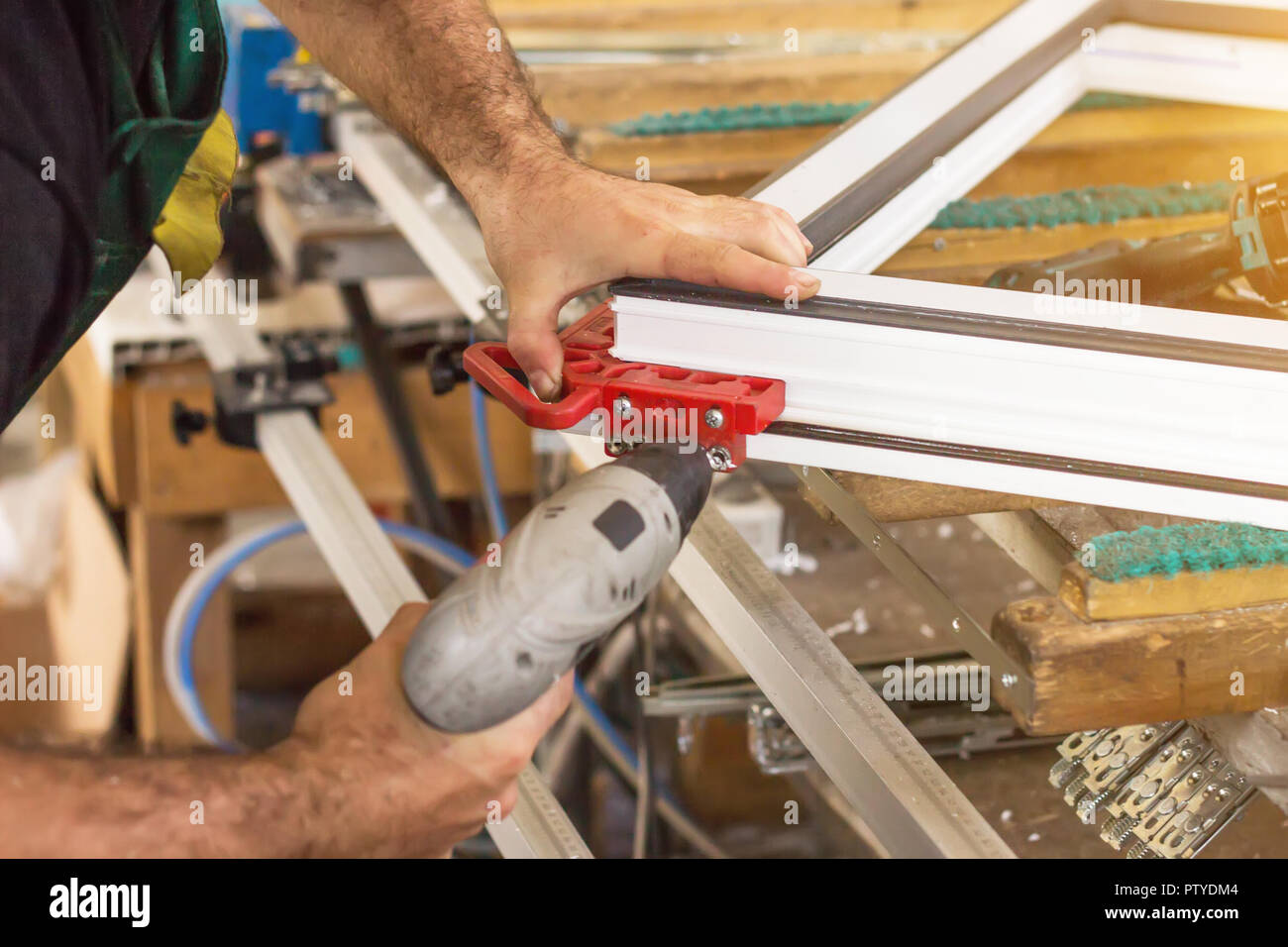 Production of pvc windows, a man screws a screwdriver into a pvc window, close-up, windows pvc - Stock Image
