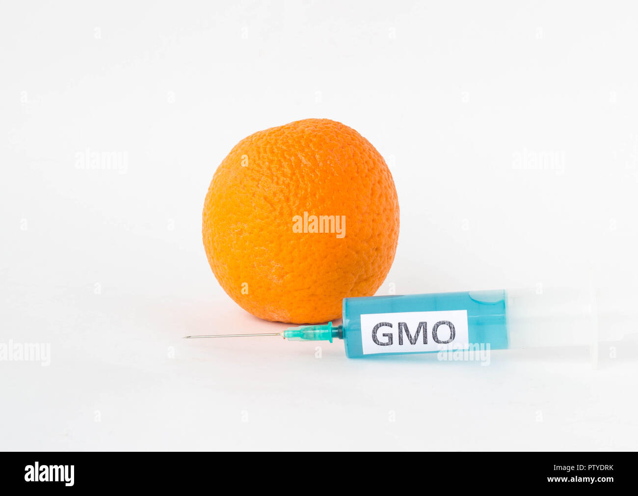 Orange on a white background near the syringe with the inscription of the GMO, close-up, genetically modified organism, orange - Stock Image
