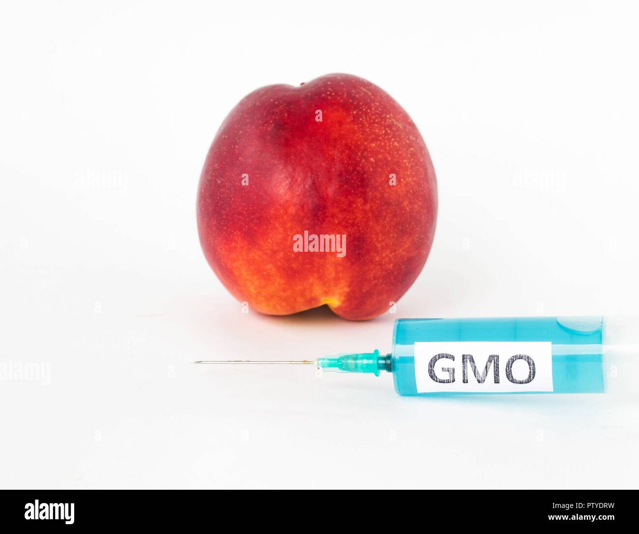 Nectarine on a white background, next is a syringe with gmo and nitrates, close-up, genetically modified organism - Stock Image